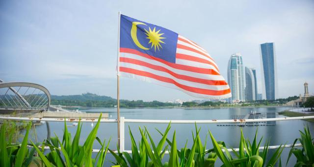 Malaysian Flag Waving Against Lake In City